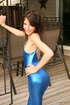 Gorgeous brunette nymph posing in blue spandex outfit on the terrace outdoors.